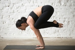 Middle aged yogi attractive woman practicing yoga concept, standing in Crane exercise, Bakasana pose, working out, wearing sportswear, black tank top and pants, full length, white loft background