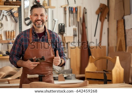 Middle ages handsome carpenter finished creating cabriolet legs and smiles to the camera/Happy Carpenter