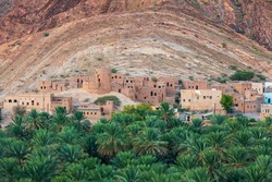 Middle East, Arabian Peninsula, Oman, Ad Dakhiliyah, Nizwa. Palm trees and a traditional mountain village in Nizwa,Oman.