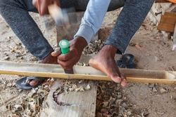 Middle East, Arabian Peninsula, Oman, Al Batinah South, Sur. Worker chiseling bamboo at a boatyard in Oman.