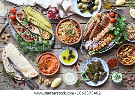 Middle eastern, arabic or mediterranean dinner table with grilled lamb kebab, chicken skewers  with roasted vegetables and appetizers variety serving on rustic outdoor table. Overhead view. #1063595402