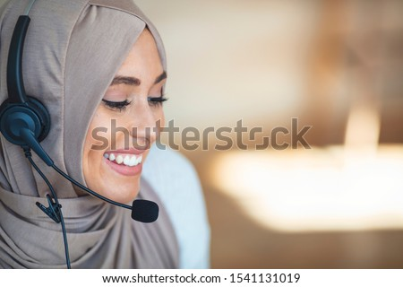 Middle eastern businesswoman with headphones closeup head shot. Young friendly Arabic operator woman agent with headsets working in call center. Beautiful Asian Muslim woman working in call center