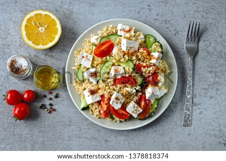 Middle Eastern cuisine. Vegetarian salad with bulgur, vegetables and feta cheese. Fresh bright arabic salad. Tabbouleh salad.