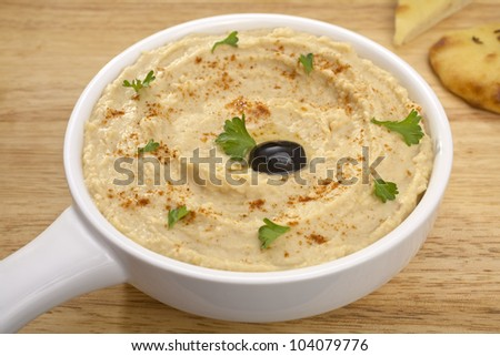 Middle Eastern dip hummus, drizzled with olive oil, sprinkled with paprika and scattered with parsley, and flat bread for dipping. - stock photo