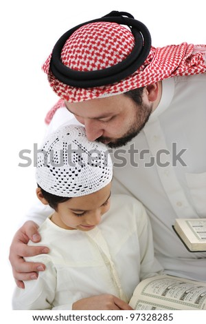 Middle eastern education father kissing son while reading Koran
