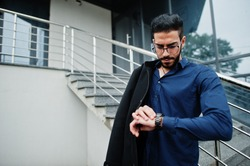 Middle eastern entrepreneur wear black coat and blue shirt, eyeglasses against office building look time at hand watches.