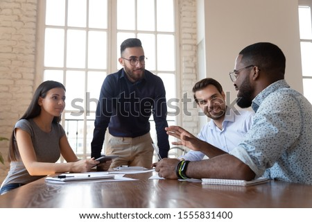 Middle eastern ethnicity office worker listening african colleague during group meeting in modern boardroom, concept of teamwork, sharing ideas, leader and associates working together on new project