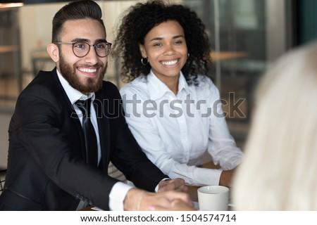 Middle eastern ethnicity satisfied businessman greeting partner shaking hands showing gratitude and respect diverse businesspeople seated at office desk or job interview successful conclusion concept