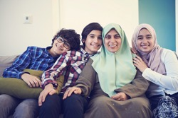 middle eastern family portrait single mother with teenage kids at home in living room