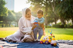 Middle eastern family with traditional dress having fun outdoors - Modern islamic mom and son in Dubai