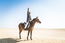 Middle eastern handsome man with typical emirates dress riding a arabic horse in the Dubai desert