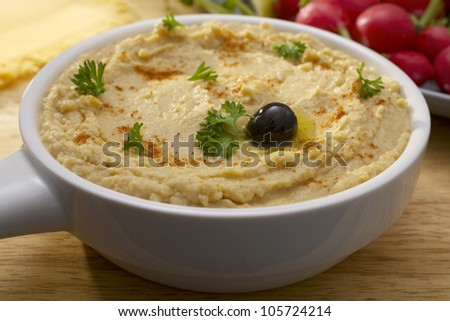 Middle Eastern hummus, sprinkled with paprika and parsley, drizzled with olive oil and topped with one black olive.