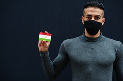 Middle eastern man in gray turtleneck and black face protect mask show Tajikistan flag isolated background.