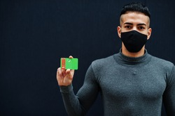 Middle eastern man in gray turtleneck and black face protect mask show Turkmenistan flag isolated background.