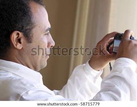 Middle eastern man shooting with point and shoot camera