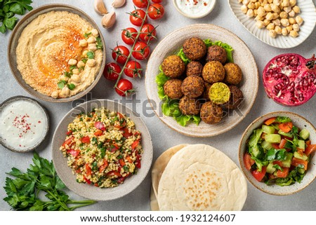 Middle eastern or arabic cuisines, falafel, hummus, tabouleh, pita and vegetables on a concrete background, view from above