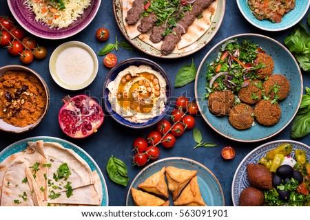 Middle eastern or arabic dishes and assorted meze, concrete rustic background. Meat kebab, falafel, baba ghanoush, muhammara, hummus, sambusak, rice, tahini, kibbeh, pita. Halal food. Lebanese cuisine #563091901