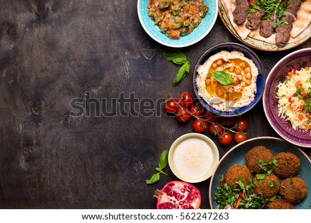 Middle eastern or arabic dishes and assorted meze on a dark background. Meat kebab, falafel, baba ghanoush, hummus, rice with vegetables, tahini, kibbeh, pita. Halal food. Space for text. Top view