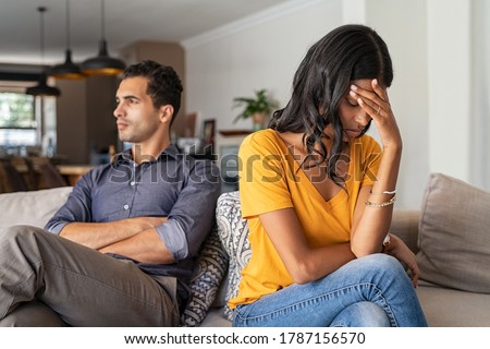 Middle eastern young couple sitting on couch after a fight. Sad indian woman sitting with hand on head after quarrel with boyfriend at home. Angry couple ignoring each other, relationship troubles.