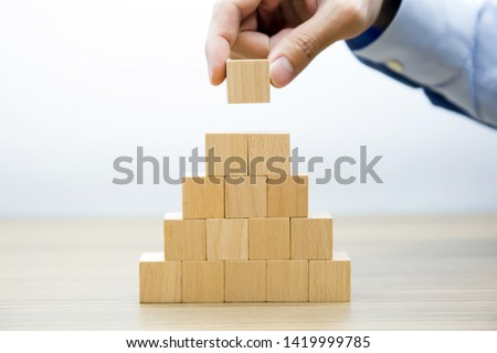 Middle  Fifteen Wooden cube Stacked in  Pyramid shape  without graphics for Business and design concept, Symbol of leadership, Teamwork and Growth. #1419999785