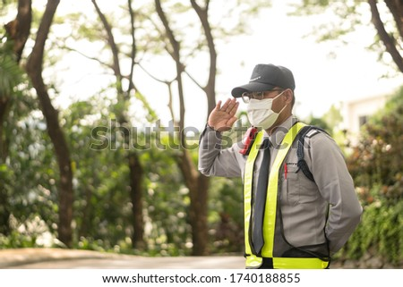 Middle old Asian security guard make saluting entry entrance the village. Security Guard Talking a portable wireless transceiver guard entrance to the village door. Speed 15 limit in area, copy space.