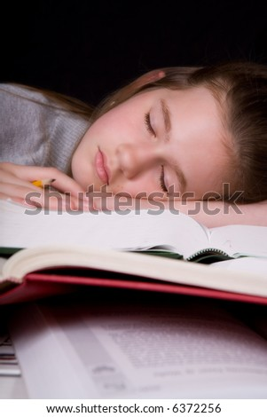 Middle school student asleep on a pile of thick textbooks, a pencil still in her hand.