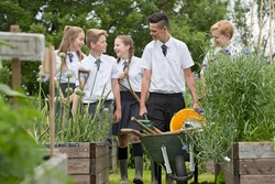 Middle school students with wheelbarrow learning gardening in vegetable garden