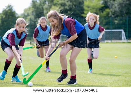 Middle schoolgirls playing hockey on the field in physical education class Foto stock ©