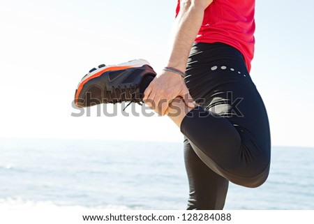 Middle section of a sports man body stretching his leg back while standing by the sea on a sunny day, against a blue sky.