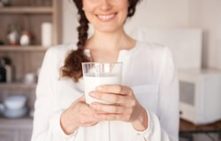 Middle section of beautiful middle age woman in home kitchen with hands holding glass of milk wearing white, faceless smiling indoors. Healthy female drinking calcium fresh organic milk, lifestyle.