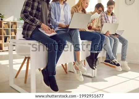 Middle section teenager secondary or high school student studying using laptop and paper copy-book, notebook sitting on classroom desk. Teen pupils involved in learning process working together Сток-фото ©