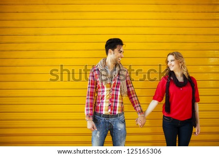 Middle shot of a young couple looking at each other and holding hands