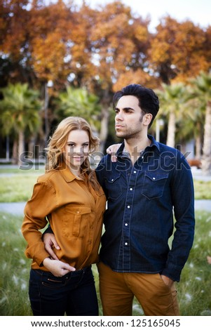 Middle shot of a young couple looking serious at the park - stock photo