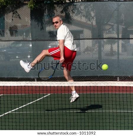Middleage man playing tennis