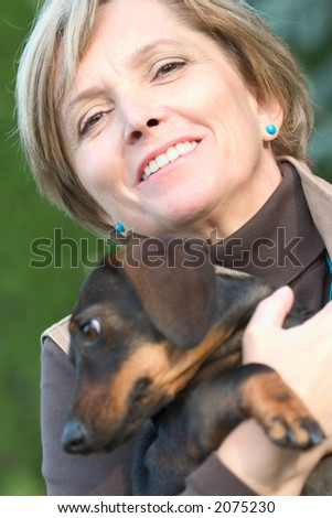 Middleaged woman carrying a small dog. Focus on woman's eyes.