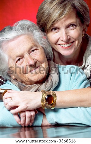 Middleaged woman hugs her mother and they both smile at the camera