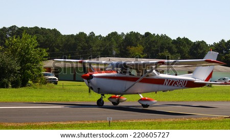 MIDDLESEX, VA - SEPTEMBER 27, 2014: A red & white personal airplane headed down the runway for takeoff in the wings wheels and keels annual show at the Hummel airfield airstrip in Middlesex VA