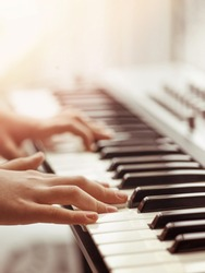 Midi keyboard or electronic piano and playing child hands. Musical education for kid in music school. Private lessons of music with a teacher for school-age children.
