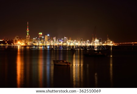 Midnight in Auckland. The lights of city downtown and the port reflected in Okahu bay with a small boat in the foreground. Soft focus