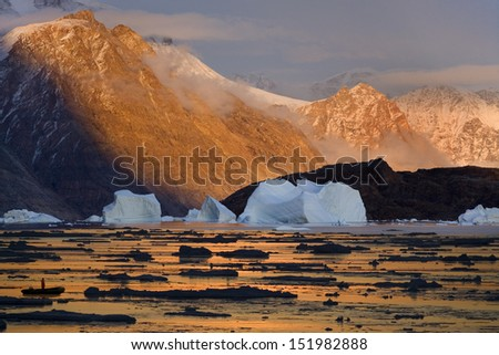 Midnight sun colors the mountains in Northwest Fjord in Scoresbysund in eastern Greenland