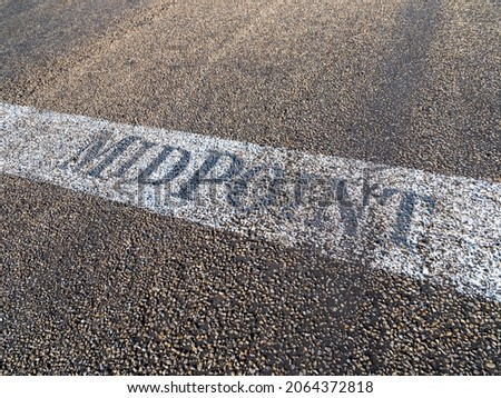 Midpoint sign painted on the Route 66 pavement at the halfway point between Chicago and Los Angeles in Adrian Texas.