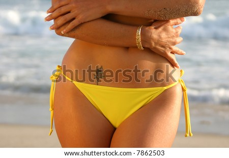 stock photo : Midriff of a Woman in a Yellow Bikini with a Rose Tattoo on