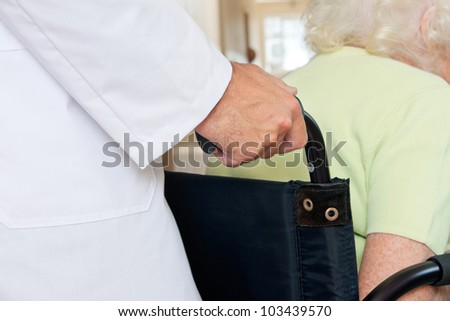 Midsection of a doctor assisting senior patient sitting in a wheel chair