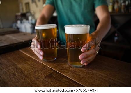 Shutterstock Midsection of bartender serving beer at counter in restaurant