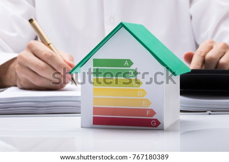 Midsection Of Businessman Calculating Invoice With Energy Efficient Chart On House Model In Office #767180389