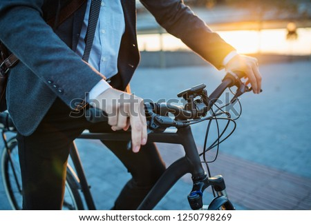 Midsection of businessman commuter with electric bicycle traveling from work in city. #1250798269