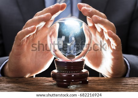 Midsection of businessman covering crystal ball at wooden table #682216924