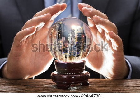 Midsection of businessman covering crystal ball with cityscape at wooden table