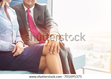Shutterstock Midsection of businessman flirting with female colleague in office