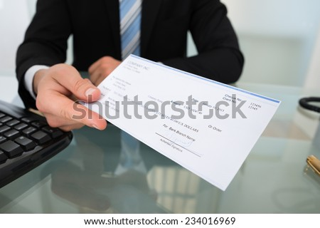 Midsection of businessman giving cheque at desk in office #234016969